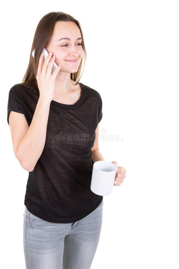 Den förbindelseunga kvinnan genom att använda den smarta mobiltelefonen som tar den varma drinken rånar in, i vit bakgrund royaltyfri fotografi