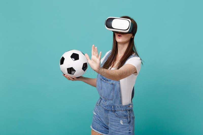 Den förbluffade ung flickafotbollsfan som ser i hörlurar med mikrofon som rymmer fotbollbollen som spelar handlag något som, skju royaltyfria bilder