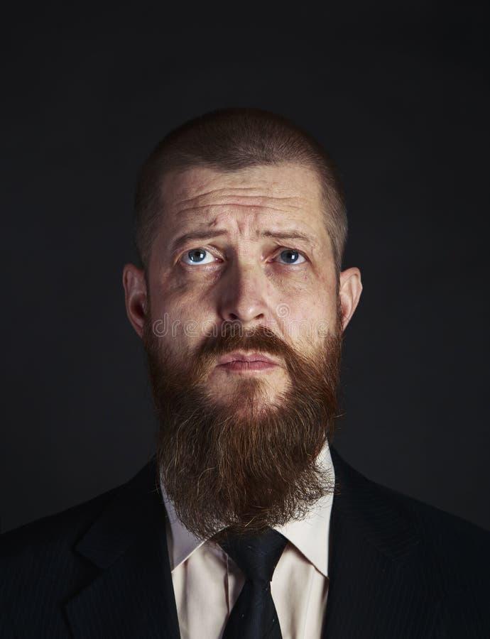 Den förbryllade ledsna skäggiga medelåldersa affärsmannen ser upp med hopp- och förfrågannärbildståenden på svart bakgrund arkivbilder