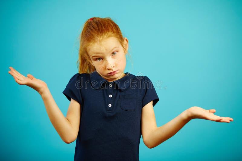 Den förbryllade röda haired flickan lyfter axelryckningar, uttrycker okunnighet av läget, eller problemet, står på blått isolerad royaltyfria bilder