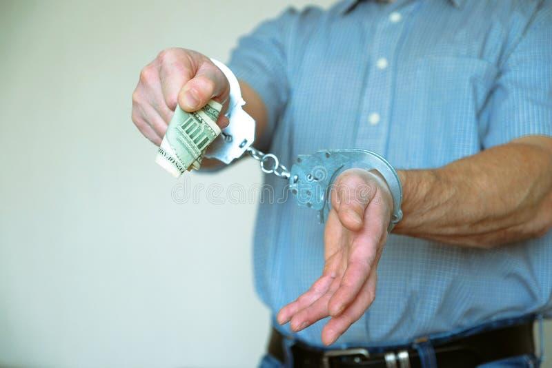 Den fördröjde brottslingen önskar att betala av polisrepresentanten Handbojor på handlederna av den fördröjde mannen fotografering för bildbyråer