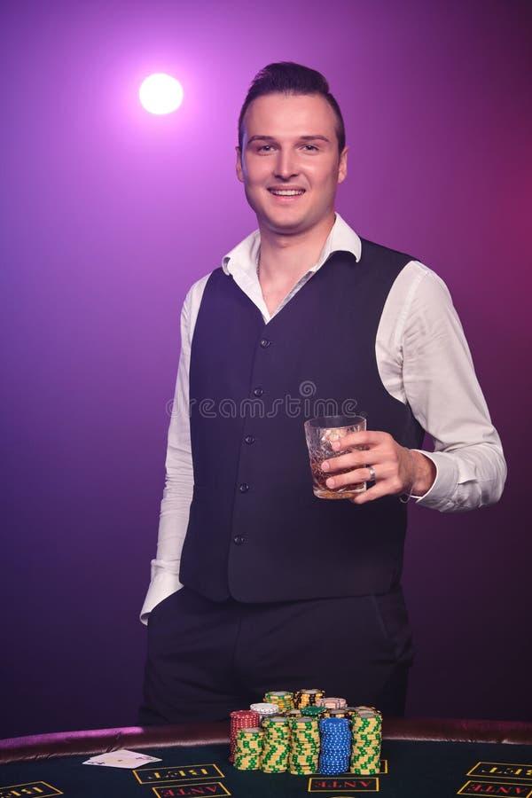 Den förmögna mannen spelar poker med en spänning på en kasino på svart bakgrund arkivfoton