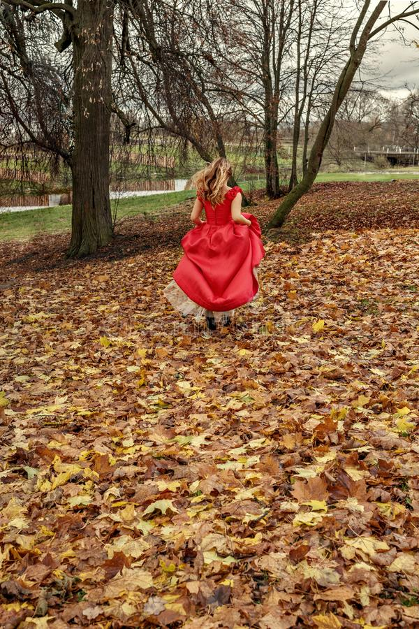 Den förrymda bruden som flickan i en röd klänning kör längs de stupade höstsidorna för stormen arkivbilder