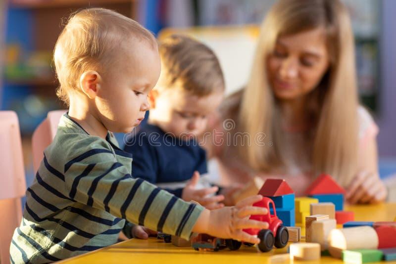 Den förskole- läraren och gulliga ungar spelar i dagis royaltyfria foton