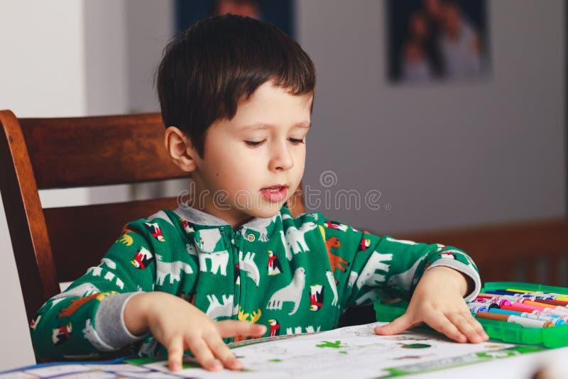 Den förskole- ungen som läser en bok, medan sitta på tabellen, shoo inomhus royaltyfria foton