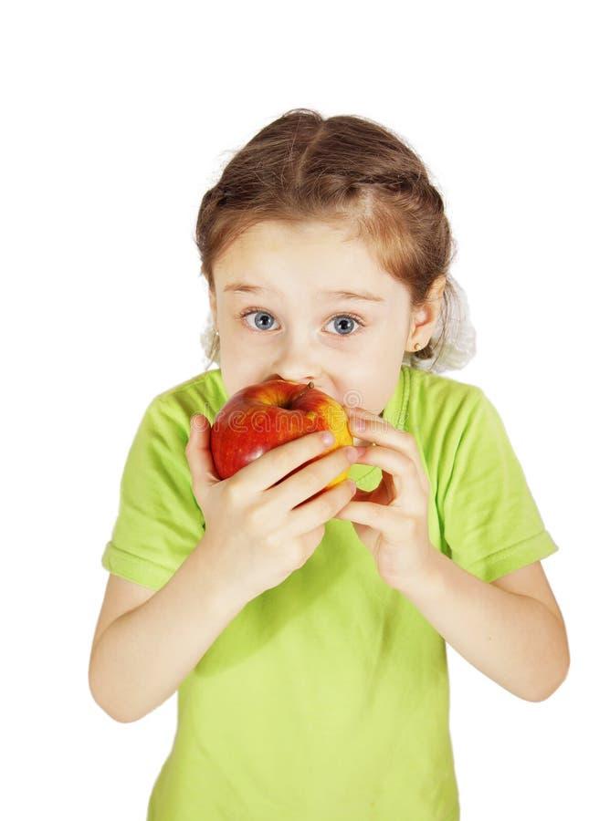 Den förskräckta lilla flickan biter ett stort rött äpple fotografering för bildbyråer