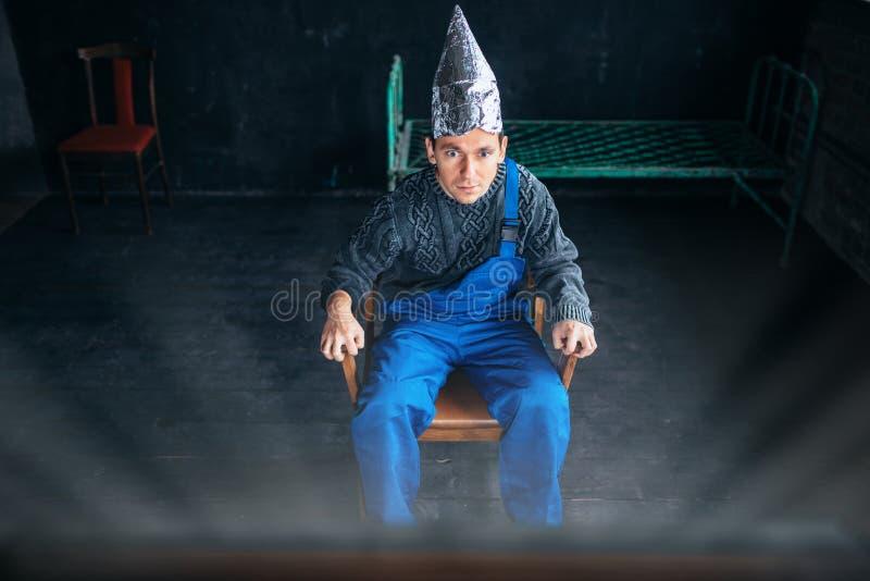 Den förskräckta mannen i hatt för aluminum folie sitter i stol royaltyfria foton