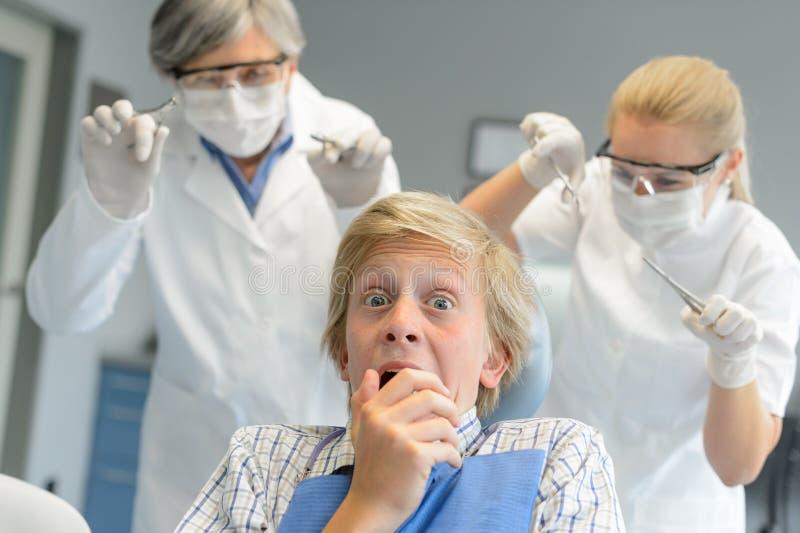 Den förskräckta tonårs- patienten skrämmer tandläkaren och sjuksköterskan arkivbild
