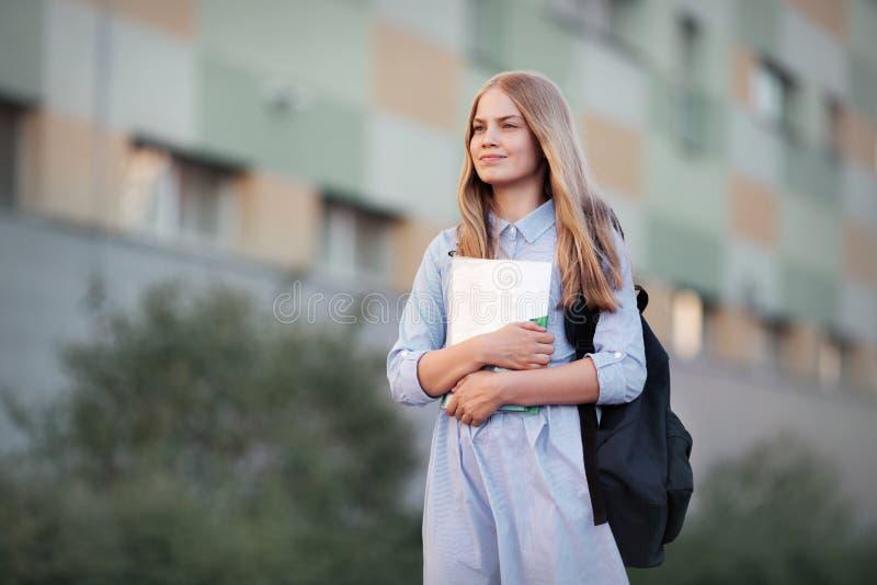 Den första dagen tillbaka till skola högstadiumflickastående av den tonåriga modellen med långt blont hår med ryggsäcken, läroböc arkivbilder