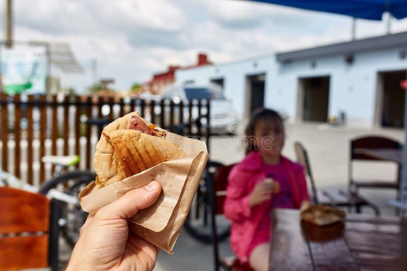 Den första personsikten sköt av en man och en flicka som äter hamburgaren i gatakafét, den mjuka fokusen, grunt djup av fältet arkivbilder