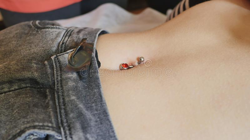 Den första piercingen Klä örhängena på naveln Kvinnlig piercing royaltyfri fotografi