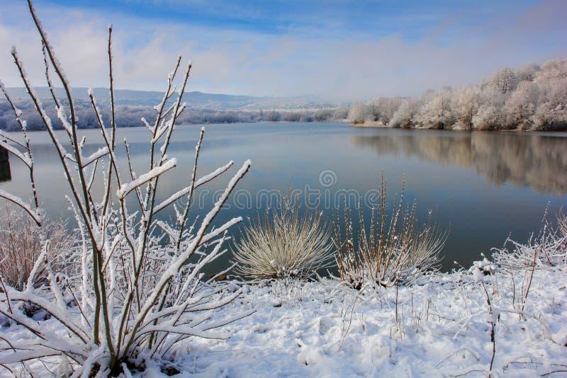 Den första snön på en bergsjö arkivfoton