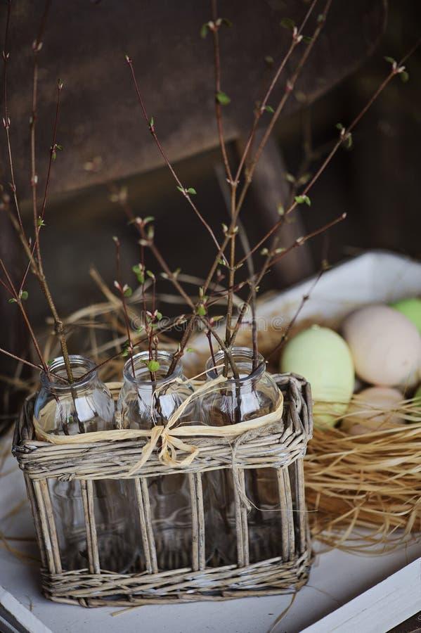 Den första våren fattar i flaskor i korg med easter ägg på bakgrund royaltyfri fotografi