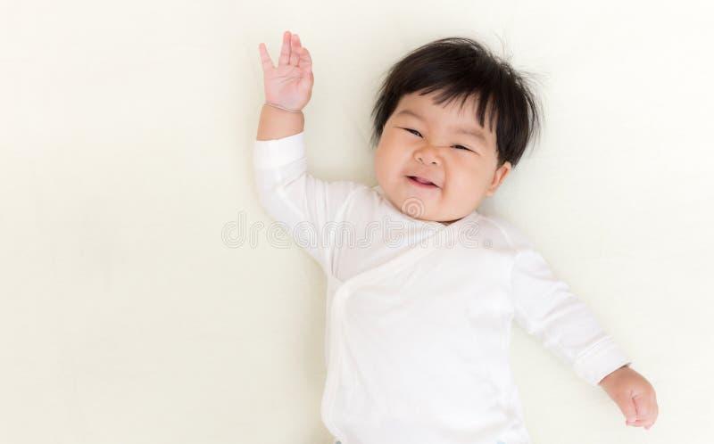 Den förtjusande asiatet behandla som ett barn flickaleende och visar handen upp på sängen fotografering för bildbyråer