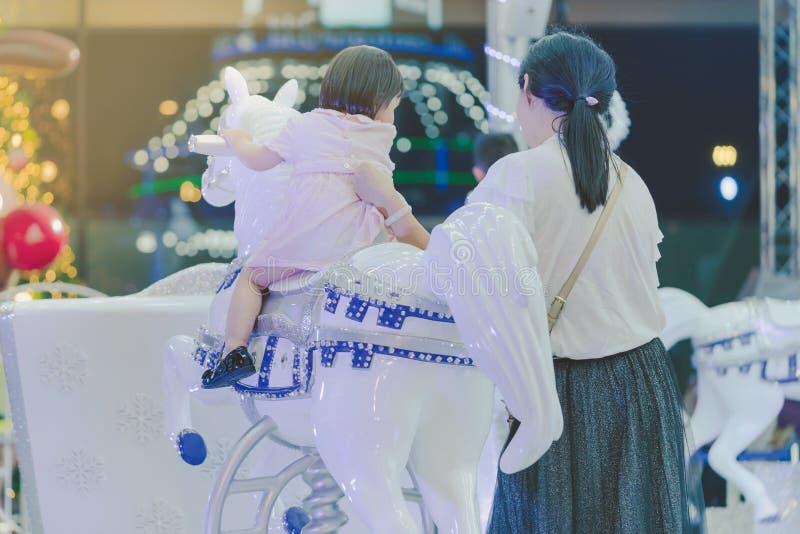 Den förtjusande asiatiska flickaridningen för den lilla ungen på ett glat går den carous rundan royaltyfri foto