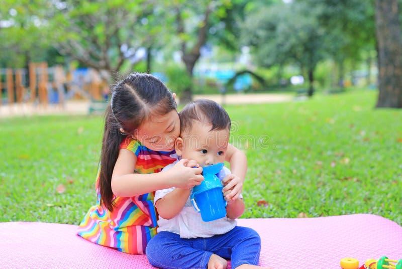 Den förtjusande asiatiska systern som sitter på mattt tagande för rosa madrass för att att bry sig hennes lilla broder till drick arkivbilder