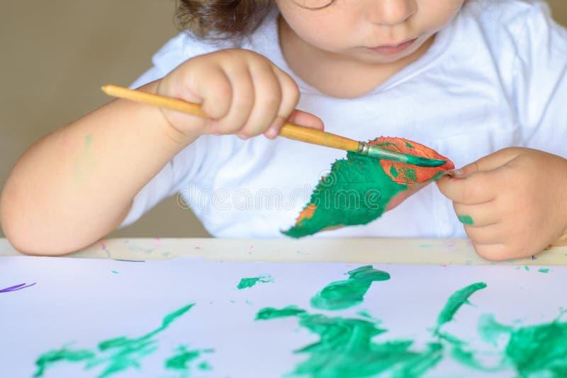 Den förtjusande barnmålningnedgången lämnar på tabellen arkivbilder