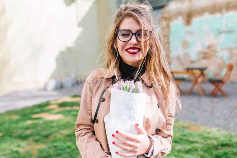 Den förtjusande blonda flickan i stilfulla exponeringsglas köpte en bukett av härliga blommor för hennes moder Närbildstående av  arkivbild