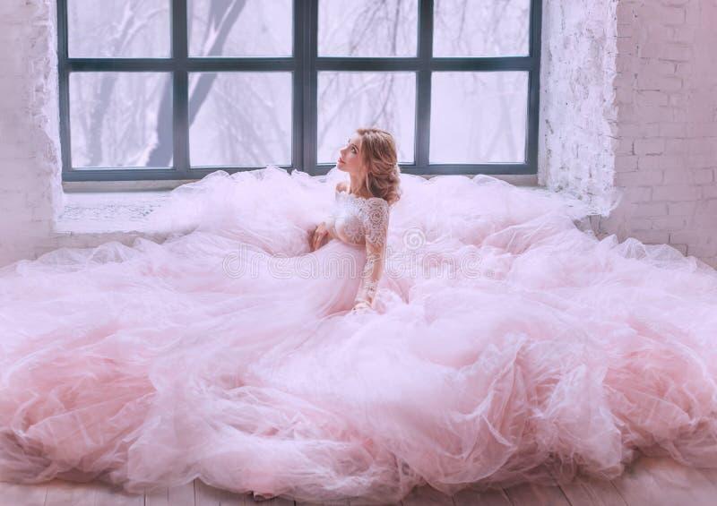 Den förtjusande damen ser playfully upp, en gravid blond flicka på golvet med en underbar frisyr, i eleganta rosa färger royaltyfri bild
