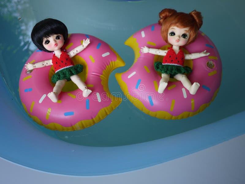 Den förtjusande dockan för BJD-bollskarven brännmärkte LATI i baddräkt De är klara att spela vatten med färgrika pölflöten royaltyfri bild