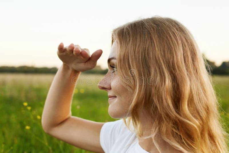 Den förtjusande flickan med ett angenämt leende och ljust rakt hår ser royaltyfri bild