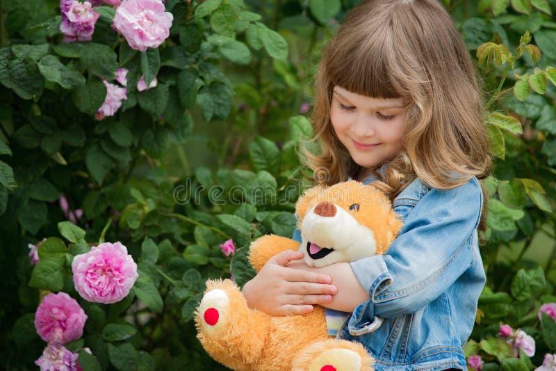 Den förtjusande le flickan med nallebjörnen parkerar in med rosa färgrosen royaltyfria foton