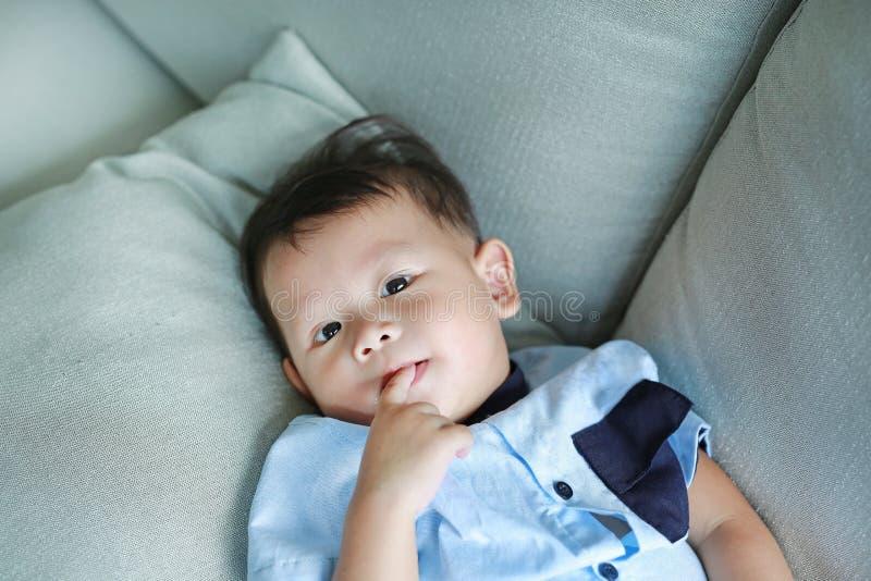 Den förtjusande lilla asiatet behandla som ett barn pojken som suger fingret i munnen som ligger på den gråa soffan arkivbild