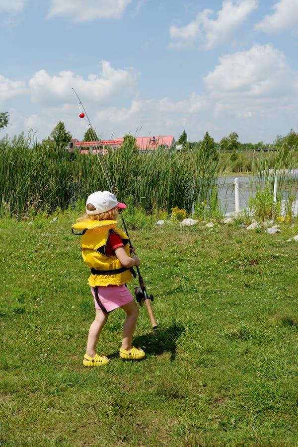 Den förtjusande lilla blonda Caucasian flickan rymmer metspöet och går till sjön Hon bär i flytväst solglasögon och hatt Hon är arkivbild