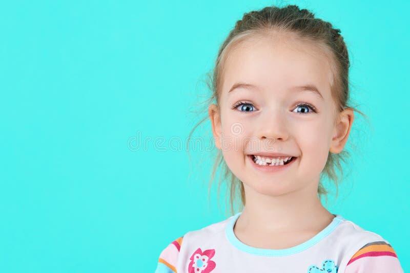 Den förtjusande lilla flickan som av ler och visar hennes första borttappat, mjölkar tanden Gullig förskolebarnstående arkivfoton