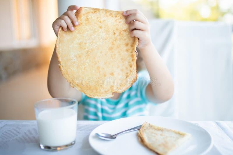 Den förtjusande lilla flickan som har frukosten, äter pannkakor och dricker, mjölkar royaltyfri fotografi