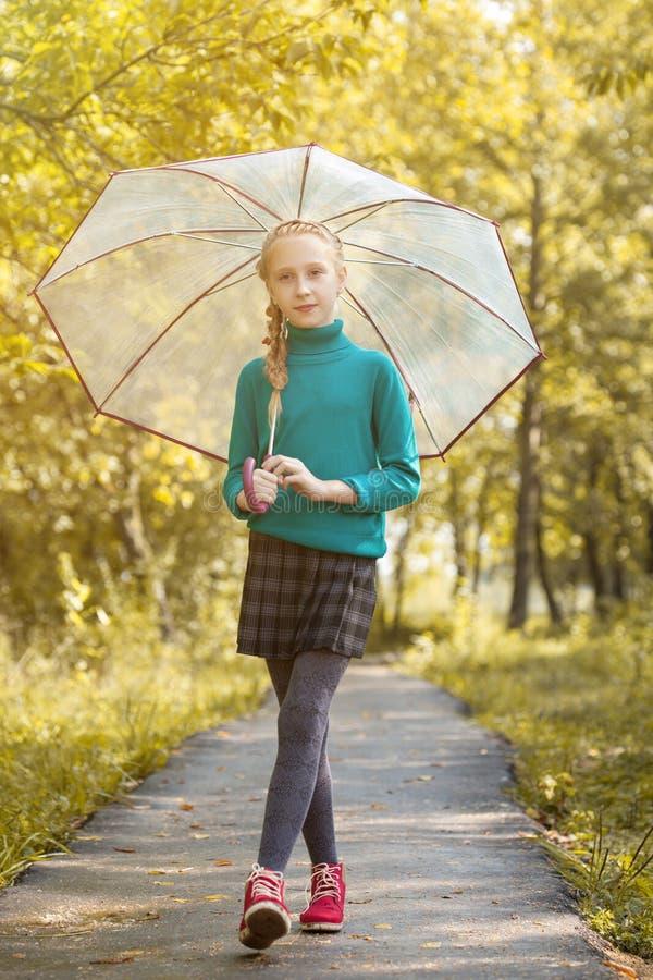 Den förtjusande lilla flickan som poserar med paraplyet parkerar in royaltyfri fotografi