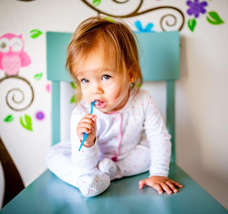 Den förtjusande litet barnflickan borstar hennes tänder i pyjamas bakgrund suddighetdde den skyddande pillen f?r maskeringen f?r  royaltyfri foto