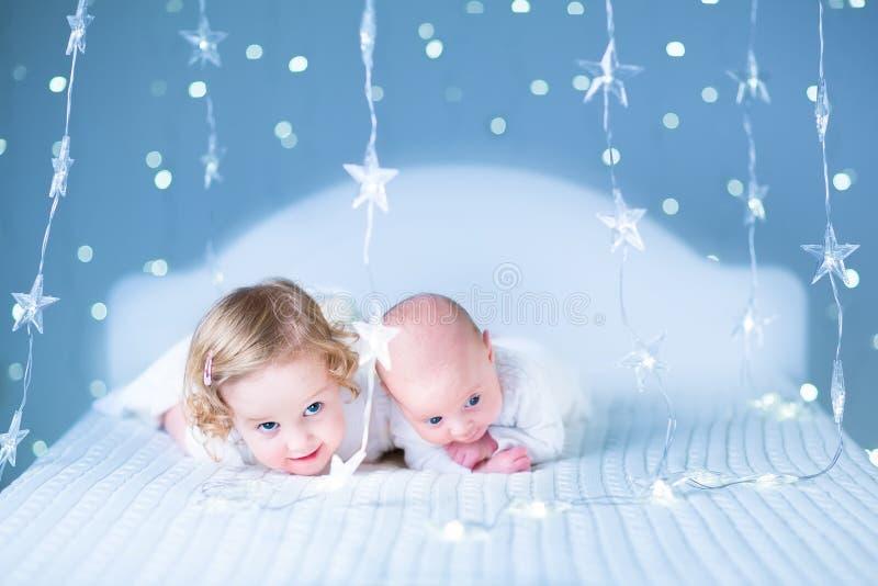 Den förtjusande litet barnflickan och hennes nyfött behandla som ett barn brodern i ljus runt om dem royaltyfri bild