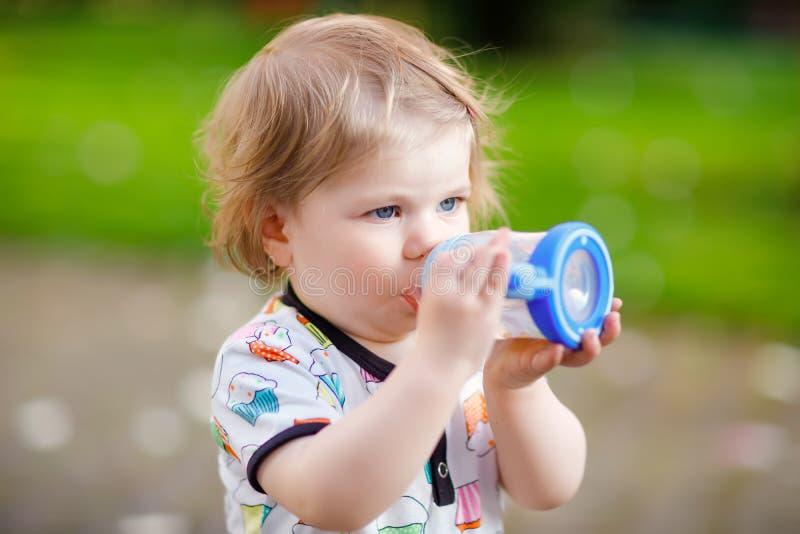 Den förtjusande litet barnflickan som dricker formel, mjölkar eller bevattnar från flaskan Gulligt lyckligt behandla som ett barn royaltyfri foto