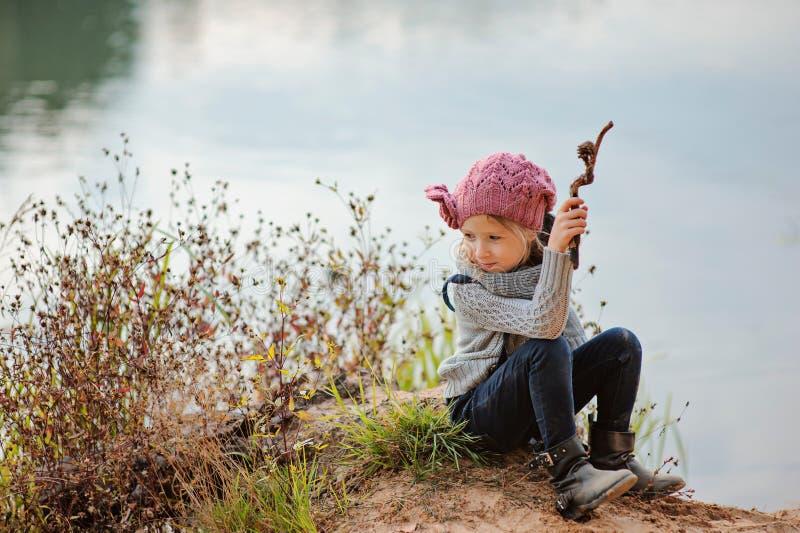 Den förtjusande lyckliga barnflickan spelar med pinnen på flodsida i solig dag royaltyfria bilder
