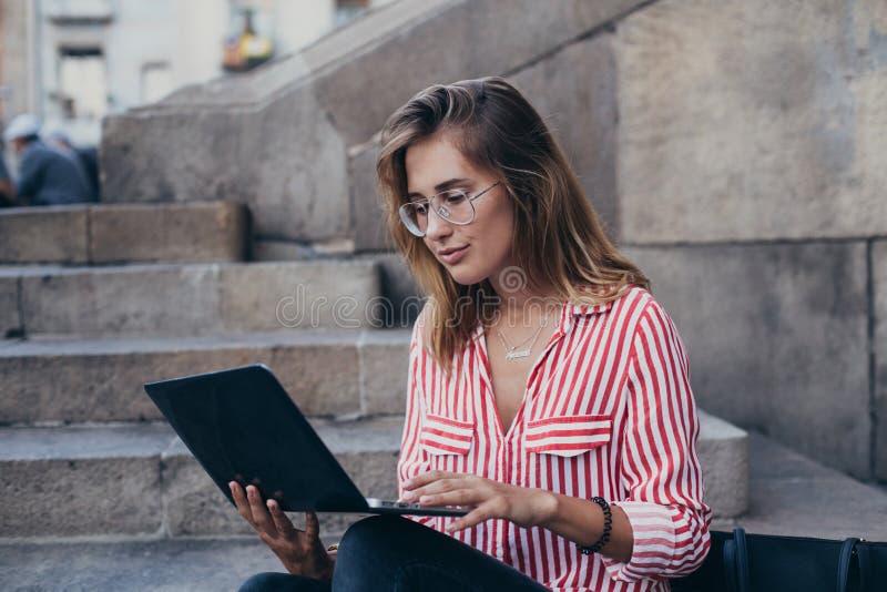 Den förtjusande nätta studenten sitter på trappa med bärbara datorn fotografering för bildbyråer