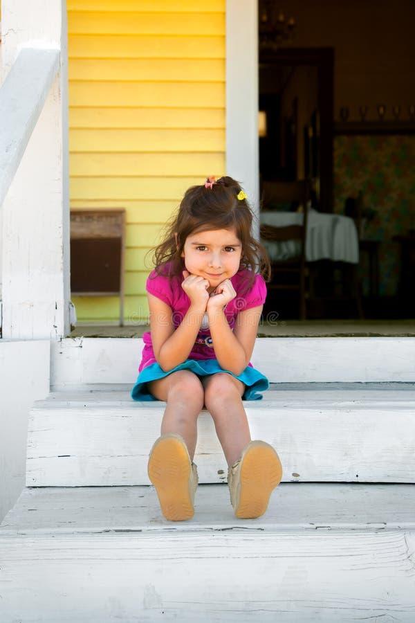 Den förtjusande unga flickan sitter på målade vita moment med hennes haka in royaltyfri fotografi