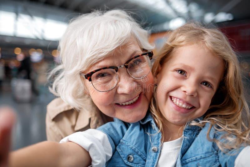 Den förtjusta gamla kvinnan och lilla flickan gör fotoet fotografering för bildbyråer