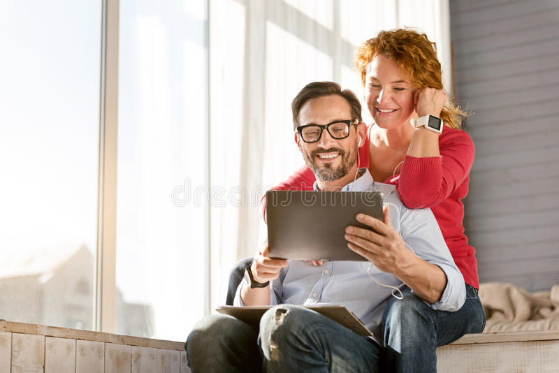 Den förtjusta mitt åldrades par som hemma tycker om musiken royaltyfria bilder