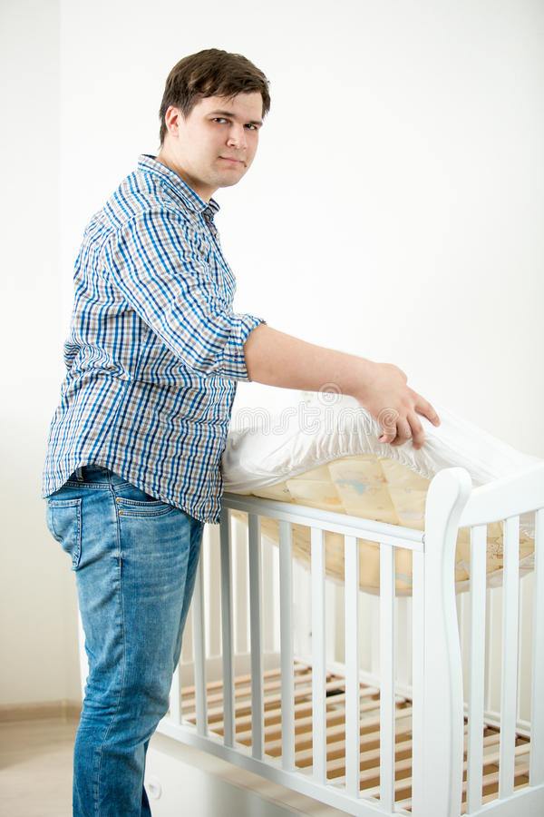 Den förväntansfulla fadern som sätter madrassen behandla som ett barn in, kåtan för ` s på barnkammaren royaltyfri bild