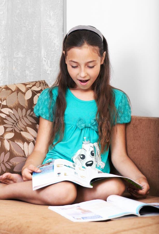 Den förvånada flickan läser en tidning royaltyfri foto