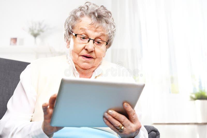 Den förvånade äldre kvinnan ser i minnestavlaskärmen arkivfoton