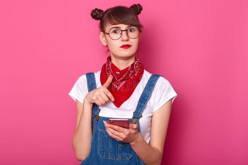 Den förvånade caucasian tonåringflickan rymmer hennes grej i handen, punkter med pekfingret på hennes smattelefon, kan inte tro,  arkivbilder