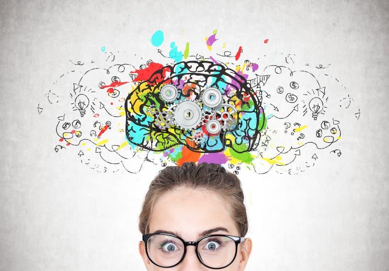 Den förvånade flickan i runda exponeringsglas, hjärna förser med kuggar royaltyfri bild