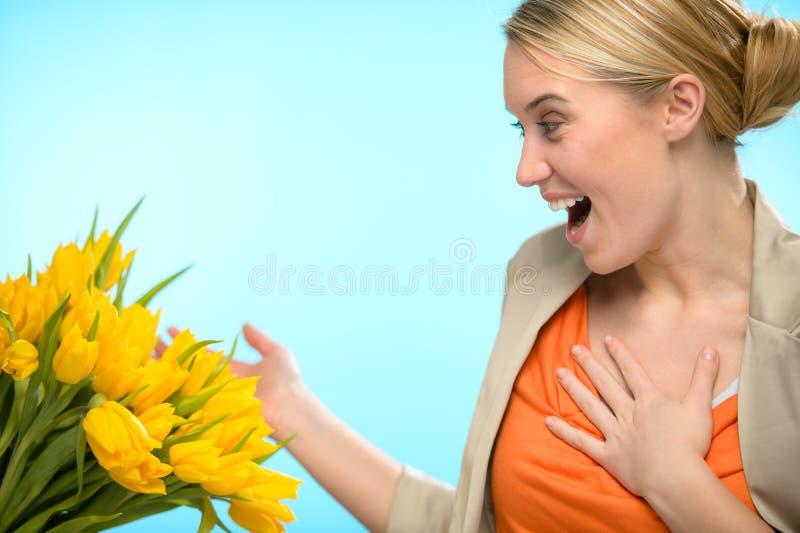 Den förvånade kvinnan mottar buketten av gula tulpan royaltyfria foton
