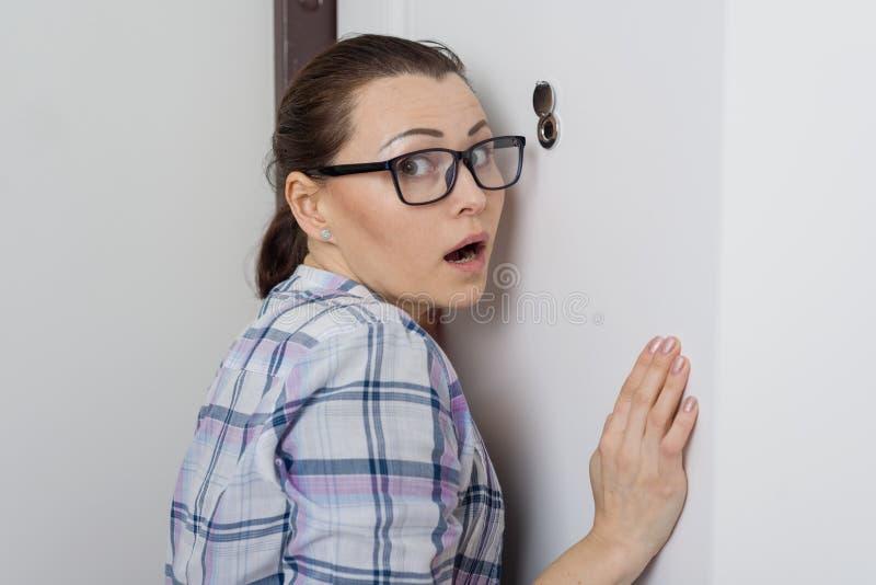 Den förvånade kvinnan ser kikhålet av ytterdörren i lägenheten royaltyfria foton