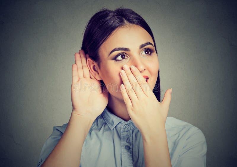 Den förvånade kvinnan som lyssnar till, skvallrar royaltyfri foto