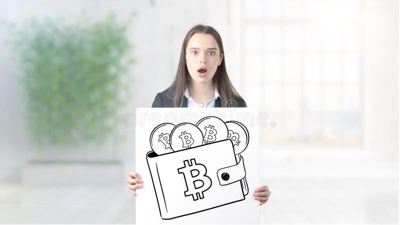 Den förvånade le unga kvinnan som bär en dräkt och ser en cryptocurrency, skissar på en designlägenhetvägg Begrepp av arkivbild