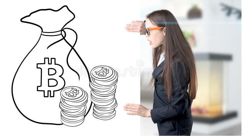 Den förvånade le unga kvinnan som bär en dräkt och ser en cryptocurrency, skissar på en designlägenhetvägg Begrepp av royaltyfria bilder