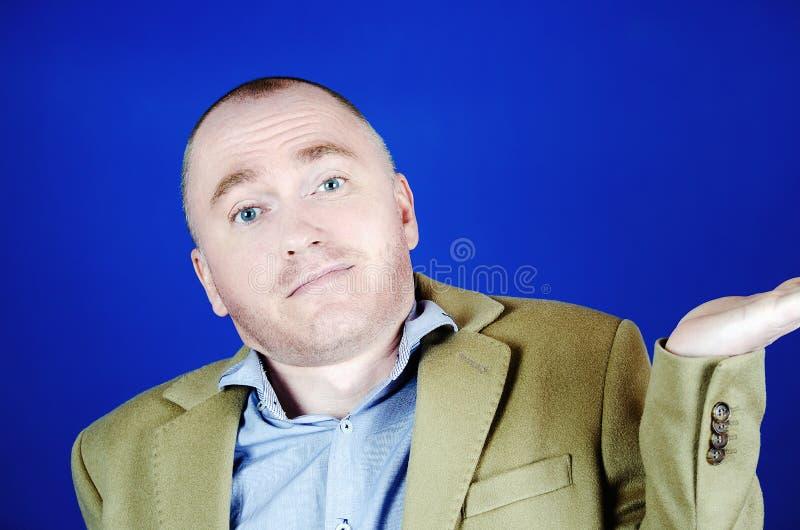 Den förvånade mannen i ett kräm- lag kastar upp hans händer till sidorna på en blå bakgrund Tomt ställe för din annonsering royaltyfria foton